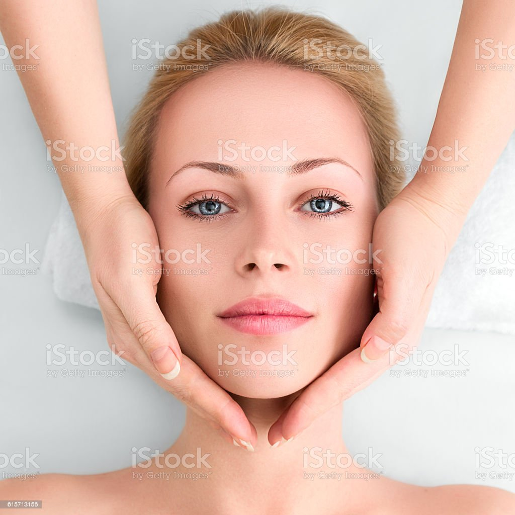 Young woman in spa gets a facial massage stock photo