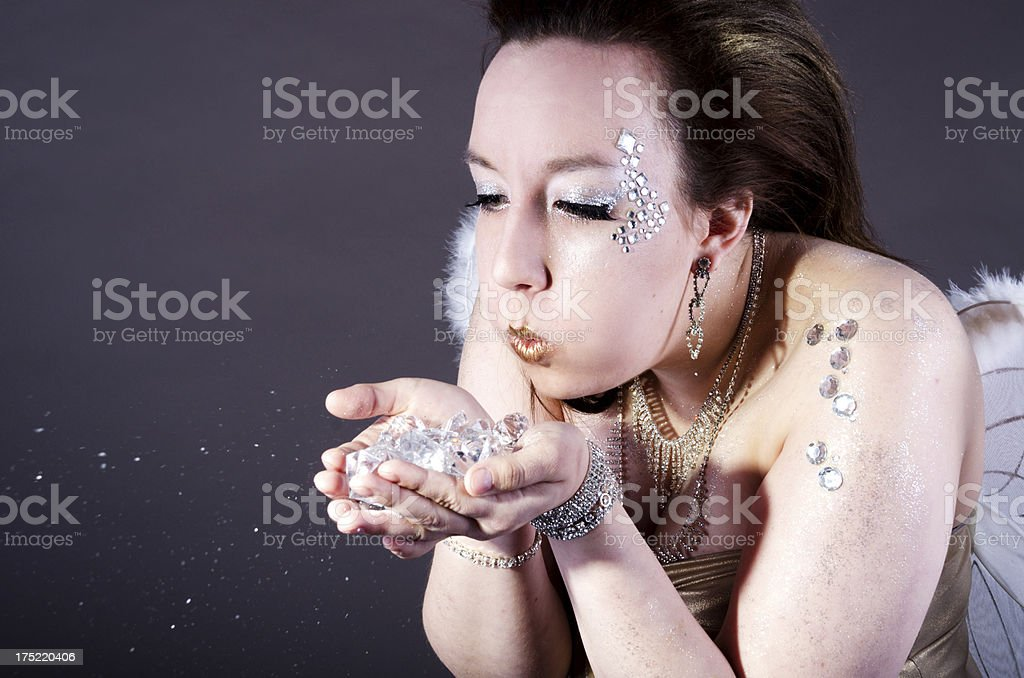 Young woman in sparkles blowing glitter. royalty-free stock photo