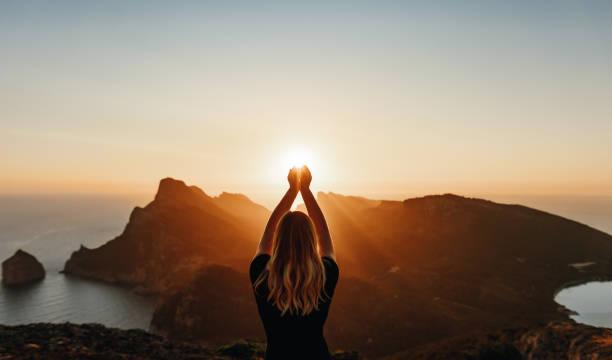 młoda kobieta w duchowej pozie trzymającej światło - nadzieja zdjęcia i obrazy z banku zdjęć