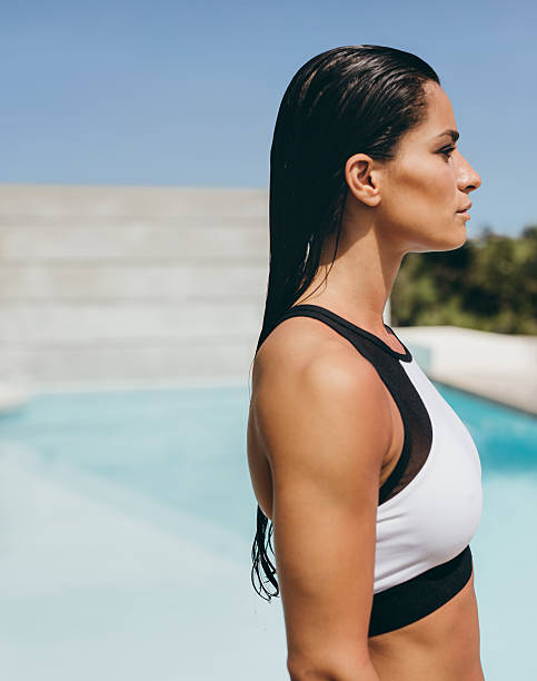 Young woman in sports bra at the poolside Side view of young woman in sports bra standing by the swimming pool. Beautiful female model in swimwear standing outdoors at the poolside. wet hair stock pictures, royalty-free photos & images
