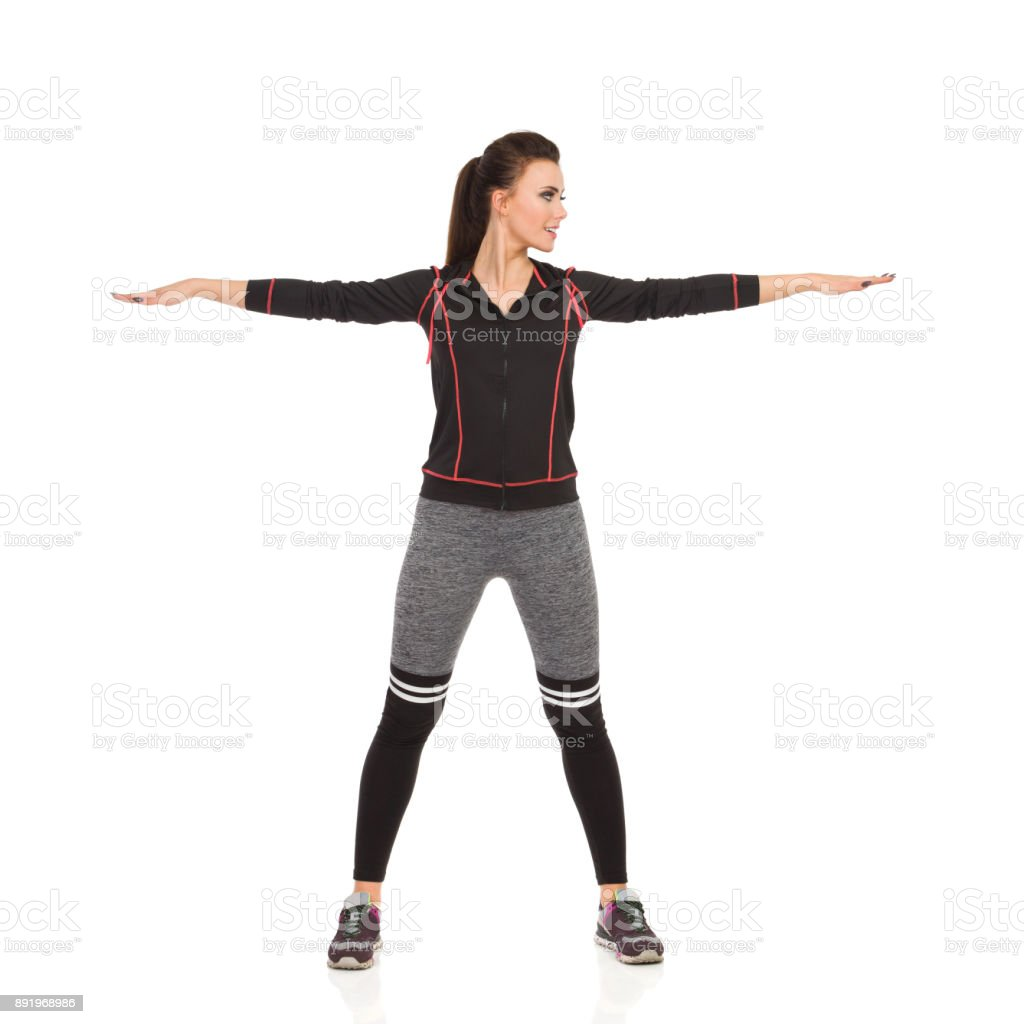 Young Woman In Sports Clothes Is Standing With Arms Outstretched And Looking Away stock photo