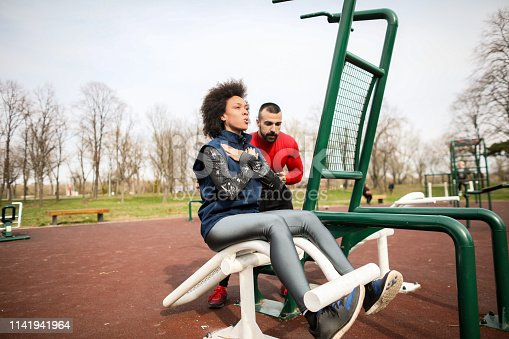 Young female athlete doing situps workout on a bench in a park with a fitness coach measuring her time and monitoring her.