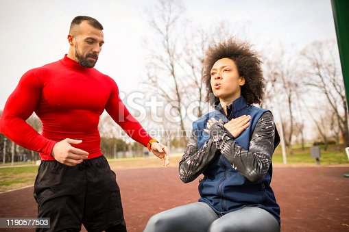 Young female athlete doing situps workout on a bench in a park with a fitness coach monitoring her.