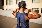 Rear view of young woman standing outdoors holding her braided hair. Fit woman in sports wear working out in city.