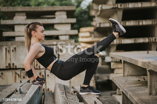 Young woman in doing stretching excersises. Young woman in sportswear training on open air.
