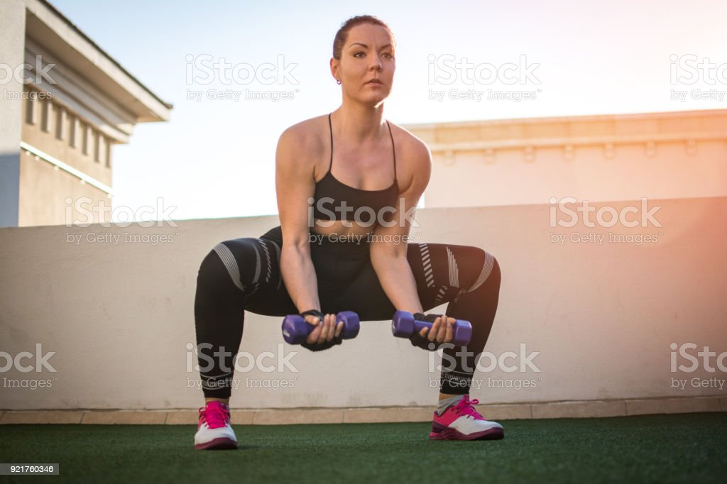 Young woman in sportswear with free weights doing squats outdoors. stock photo