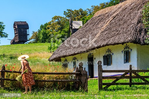 Kiev, Ukraine - June 28, 2020: Young woman in straw hat collects flowers near ancient traditional ukrainian rural house