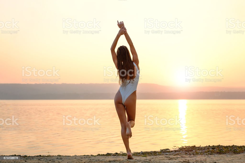 Young woman in strings swimsuit stands on the beach in sunrise stock photo