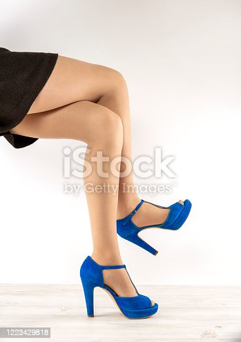 Young woman in stylish shoes on a colored background