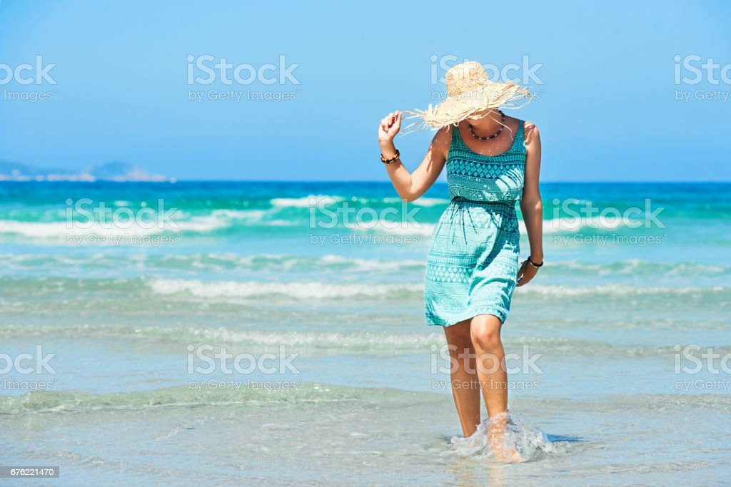 Young woman in summer dress and straw hat walking on beach. stock photo
