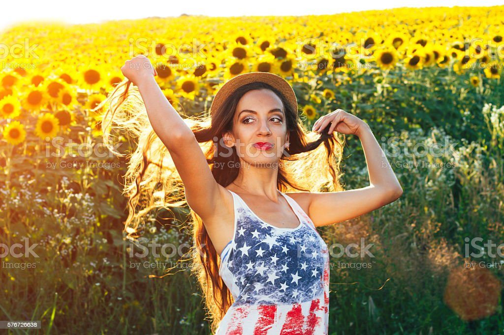 Young woman in sunflower field.american flag stock photo