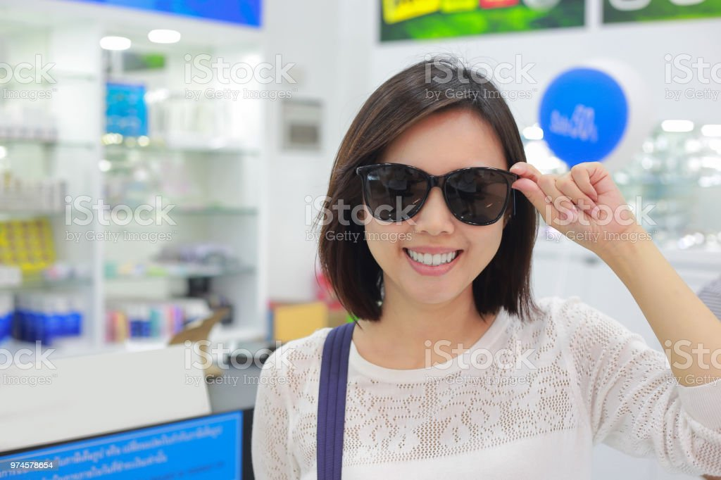 Young woman in sunglasses looking at camera in shop. stock photo