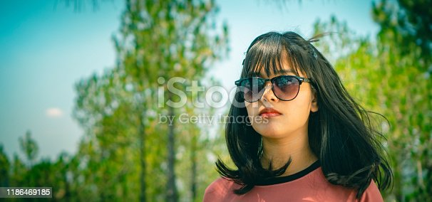 927814202 istock photo A young woman in sunglasses stands under pine trees with blank expression. 1186469185