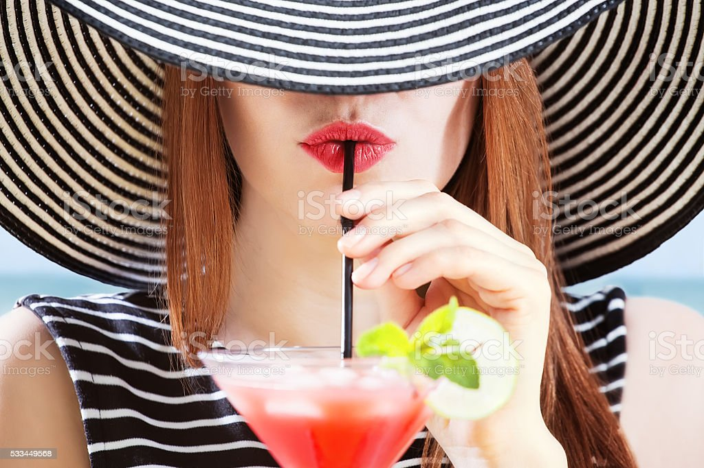 young woman in sunhat drinks cocktial stock photo