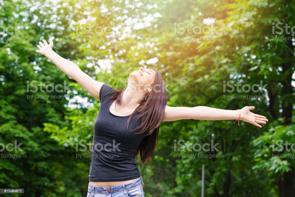 Young Woman in sunny park with outstretched arms stock photo