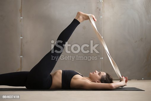 Young yogi sporty woman working out, warming up using yogic belt, lying in yoga Supta Padangushthasana, One Leg Lift exercise, reclined variation of Extended Hand to Big Toe pose, studio, side view