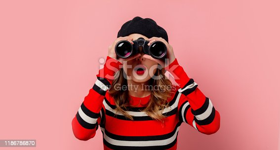 Young woman in sweater with binoculars on pink background