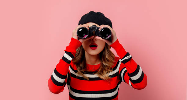 Young woman in sweater with binoculars on pink background stock photo
