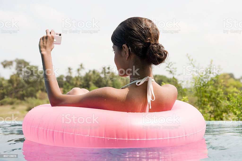 Young woman in swimming pool with camera royalty-free stock photo