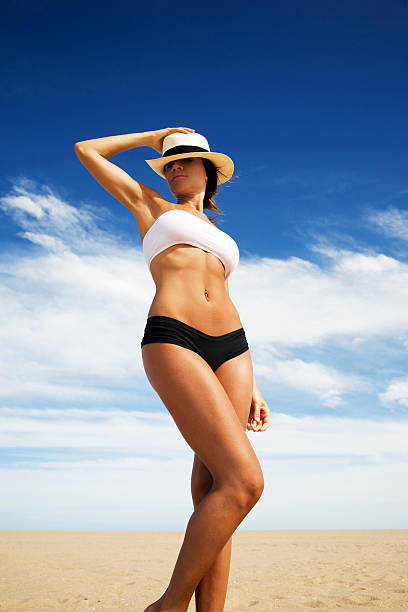 Young woman in swimsuit and hat standing on the beach stock photo