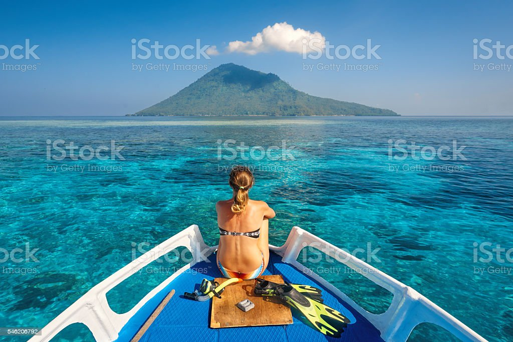 Young woman in swimsuit sit on boat mask and flippers stock photo