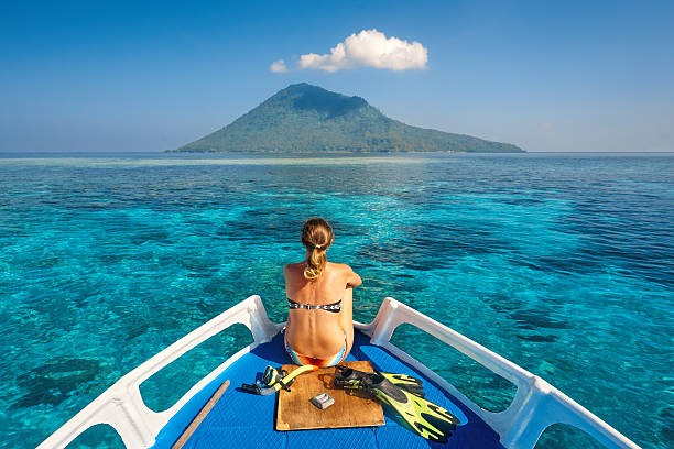 Young woman in swimsuit sit on boat mask and flippers Young woman in swimsuit sit on boat with a mask and flippers looking to a clean sea and volcano Manado Tua. North Sulawesi, Indonesia. sulawesi stock pictures, royalty-free photos & images