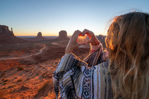 Young woman in the American desert making heart shape frame with hands loving road trip adventure stock photo
