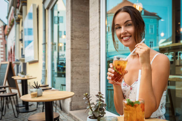 young woman in the city drinking ice tea stock photo