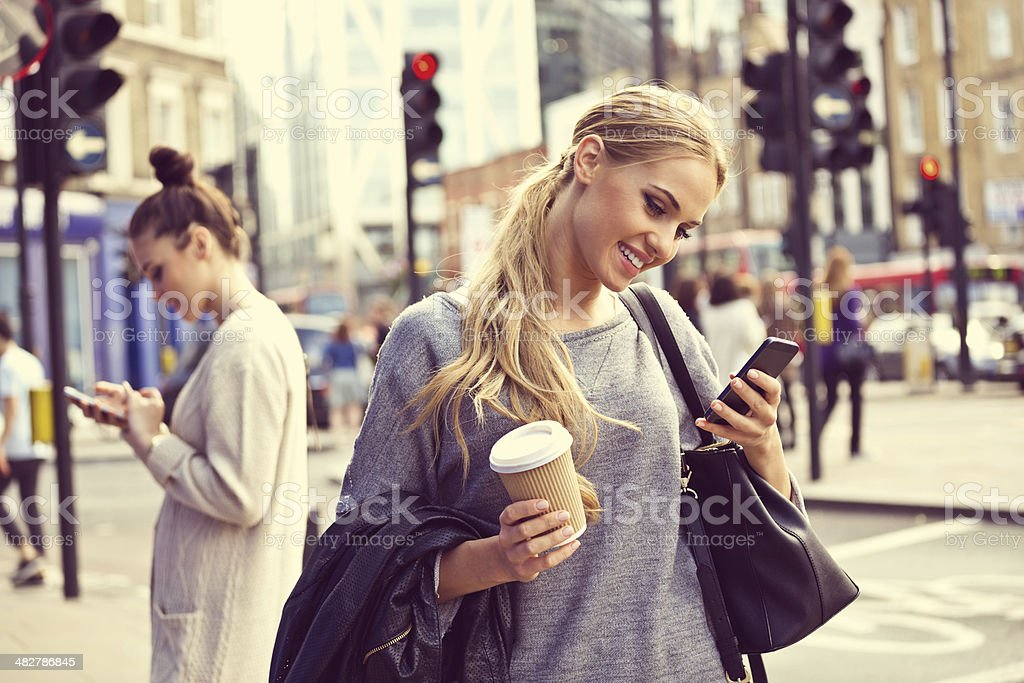 Young woman in the city Smiling young woman standing on the street and using smart phone.  20-24 Years Stock Photo