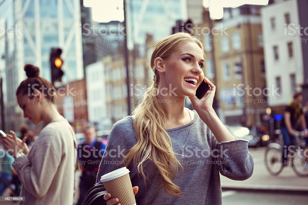 Young woman in the city Smiling young woman standing on the street and talking on the phone.  20-24 Years Stock Photo