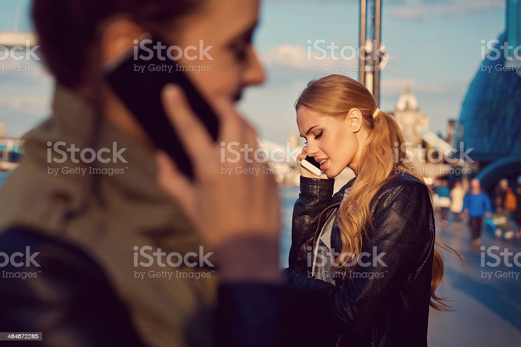 Young woman in the city Two young women standing on the street and talking on the phones. Focus on the blonde woman. 20-24 Years Stock Photo