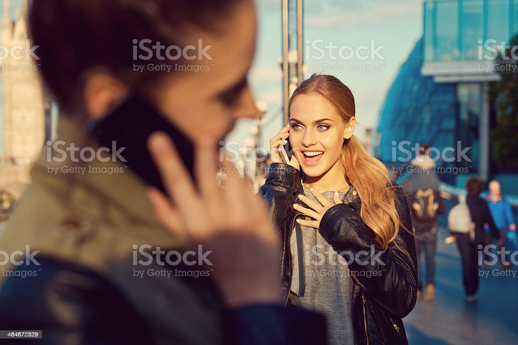 Young woman in the city Two young women standing on the street and talking on the phones. Focus on the smiling blonde woman. 20-24 Years Stock Photo