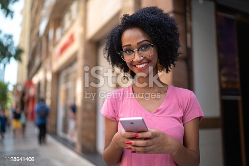 istock Young woman in the city using smartphone portrait 1128641406