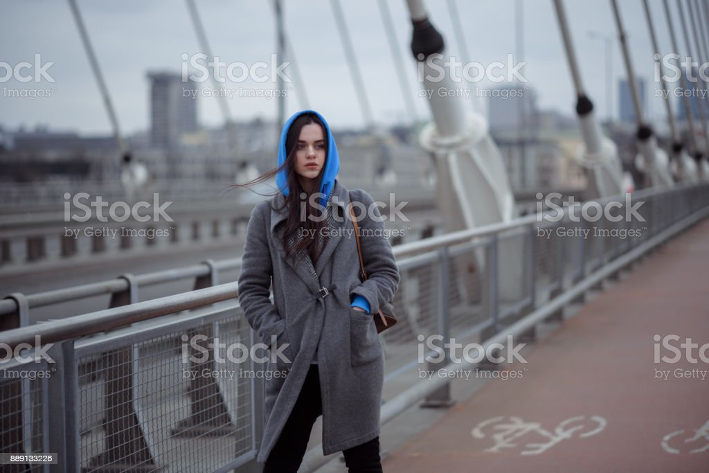 Young woman in the coat, walks on the city bridge during the windy weather. Urban autumn winter style stock photo
