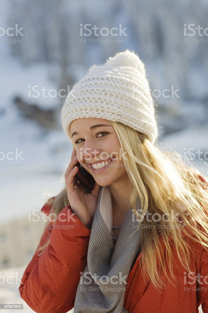 Young woman in the cold using cell phone royalty-free stock photo