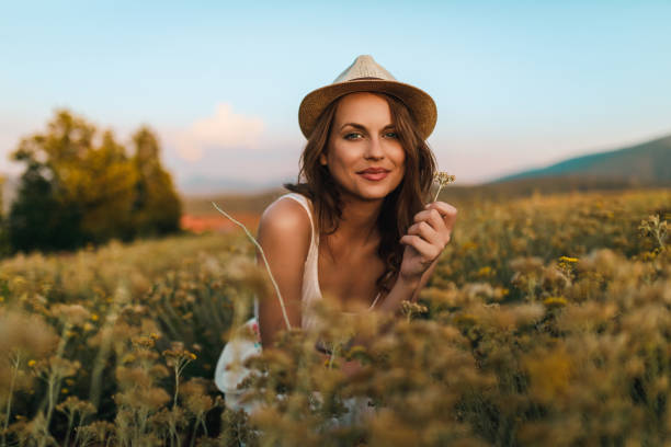Young woman in the flower field on a sunny day stock photo