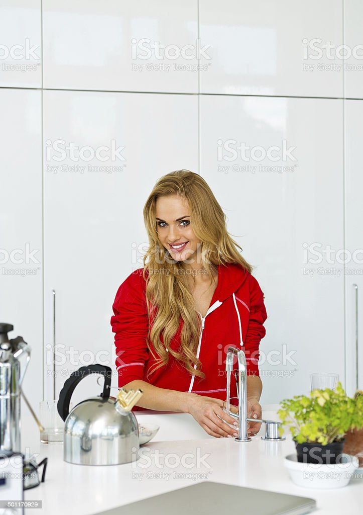 Young woman in the kitchen Young woman washing dishes in modern kitchen, smiling at the camera. 20-24 Years Stock Photo