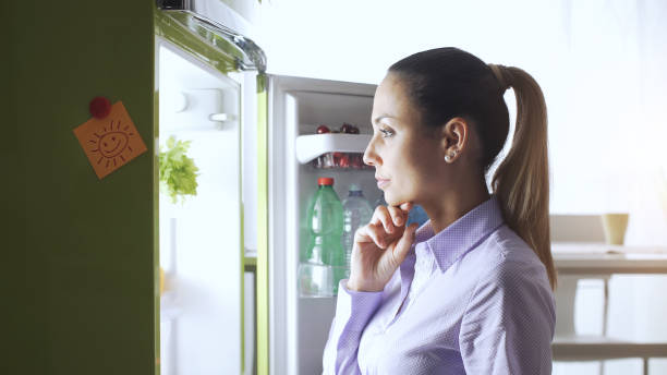 Young woman in the kitchen, she is looking into the fridge and thinking with hand on chin, food preparation and lifestyle concept stock photo