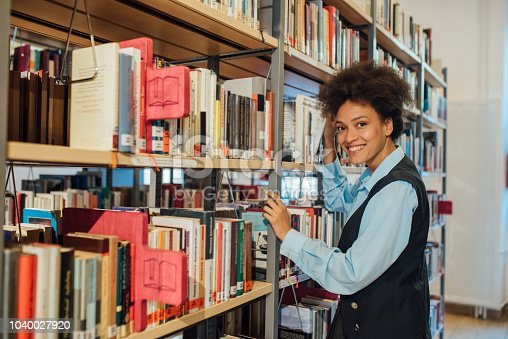 istock Young woman in the library 1040027920