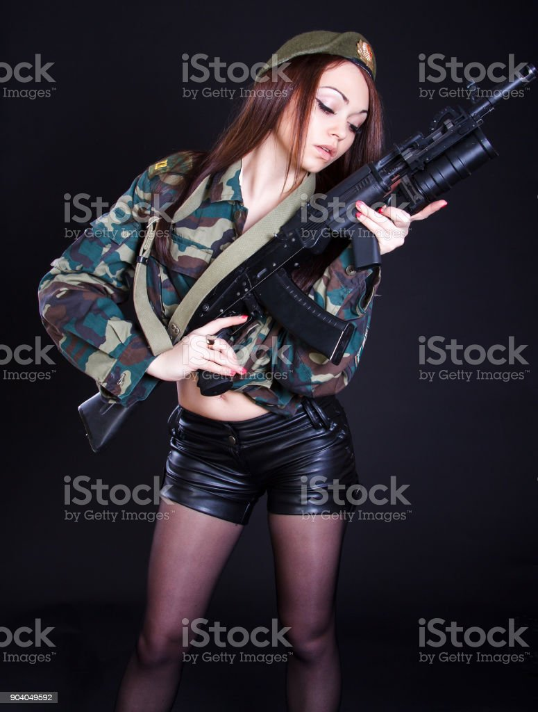 Young woman in the military uniform with the assault rifle stock photo
