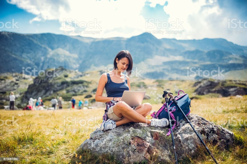 Young woman in the mountain using lap top stock photo