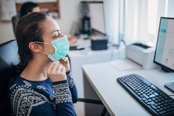 Young woman in the office putting on the protective mask, to prevent coronavirus from spreading Young woman in the office putting on the protective mask, to prevent coronavirus from spreading prevention stock pictures, royalty-free photos & images