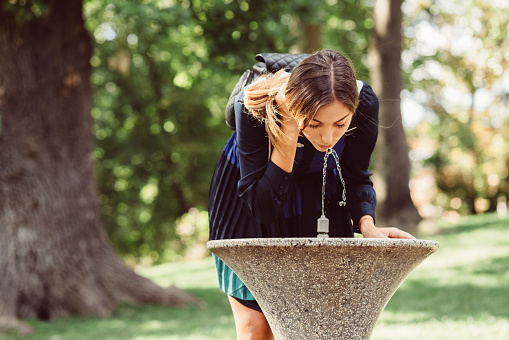 Young woman in the park drinking water at hot summer day