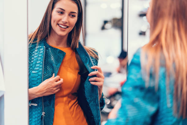 Young woman in the shopping mall enjoying a leather jacket Happy women in the clothing store coat garment stock pictures, royalty-free photos & images