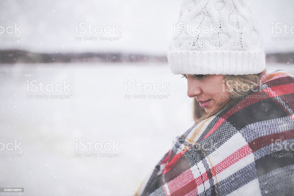 young woman in the snow wearing a checkered blanket and hat during a...