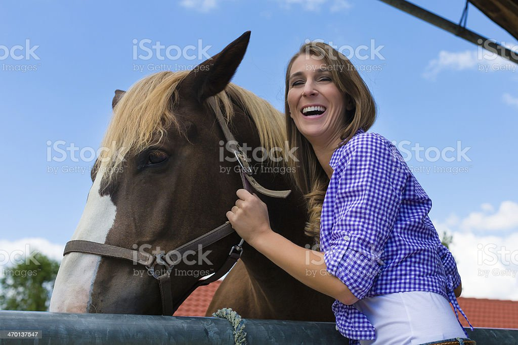 Young woman in the stable with horse stock photo