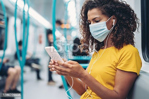 Young African ethnicity woman with a cell phone in a subway train