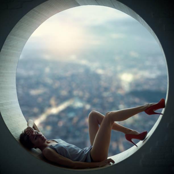 young woman in the window - dachformen stock-fotos und bilder