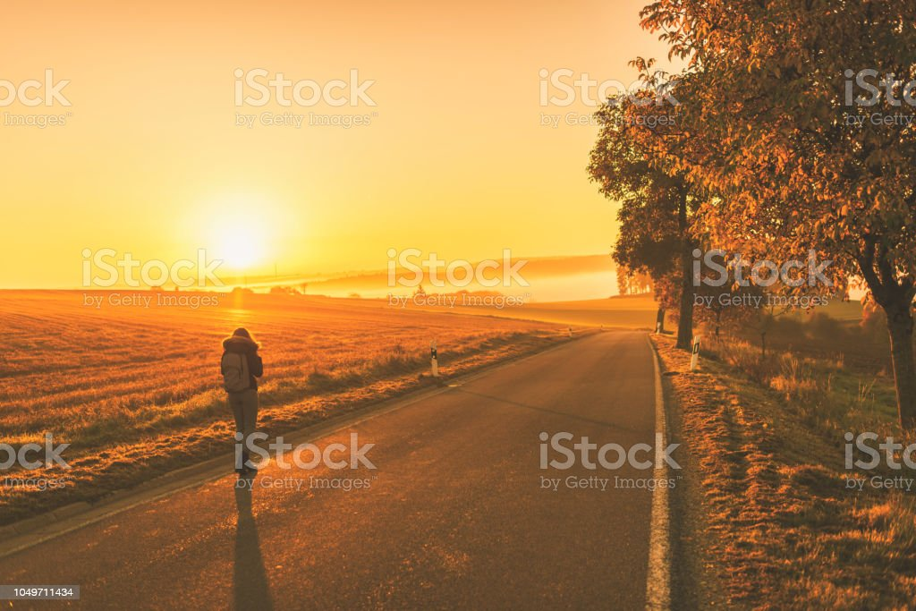 Young woman in the winter jacket with a backpack or suitcase on the road against the background of the sunrise autumn field. stock photo