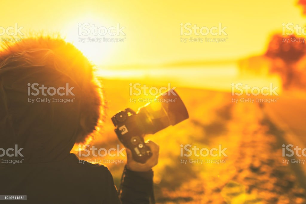 Young woman in the winter jacket with camera on the road against the background of the sunrise autumn field. stock photo